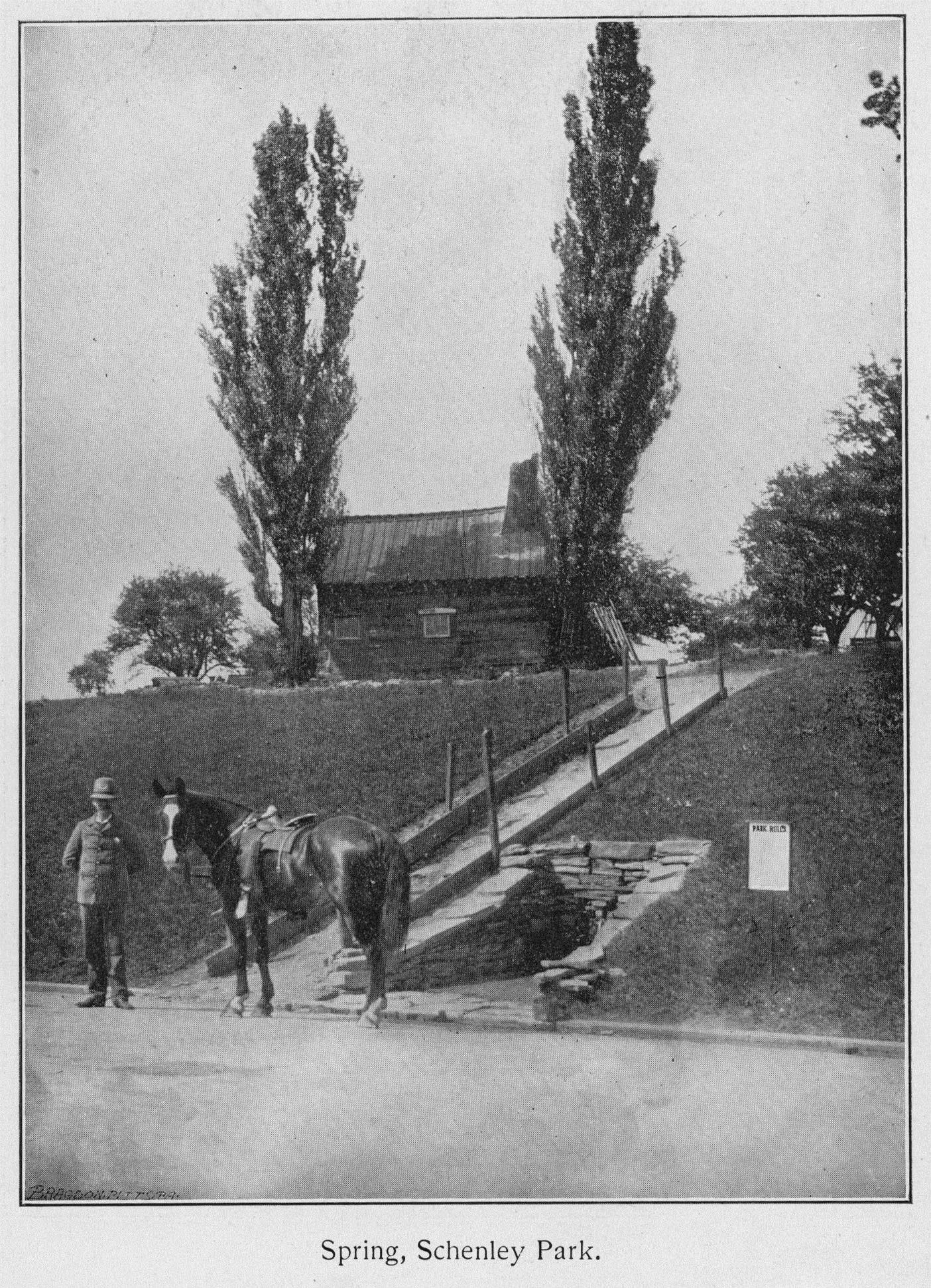photo from 1900 of Neill Log House on a hill with horse and man at the bottom of the hill