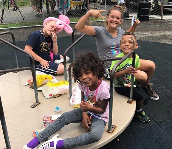Kids eating on spin-around playground ride.