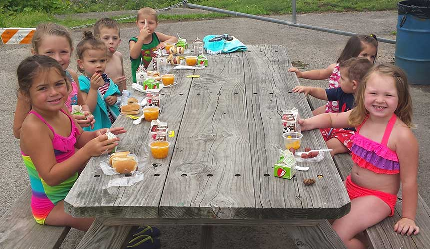 Kids eating at picnic table.